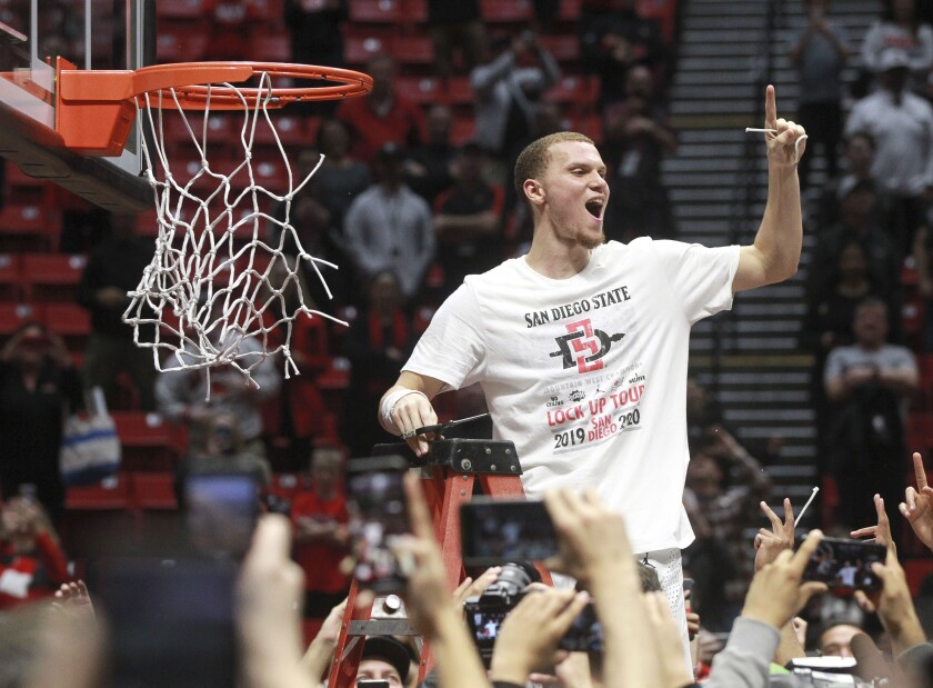SDSU's Malachi Flynn cuts down the net at Viejas Arena after Aztecs clinched Mountain West conference championship last month.