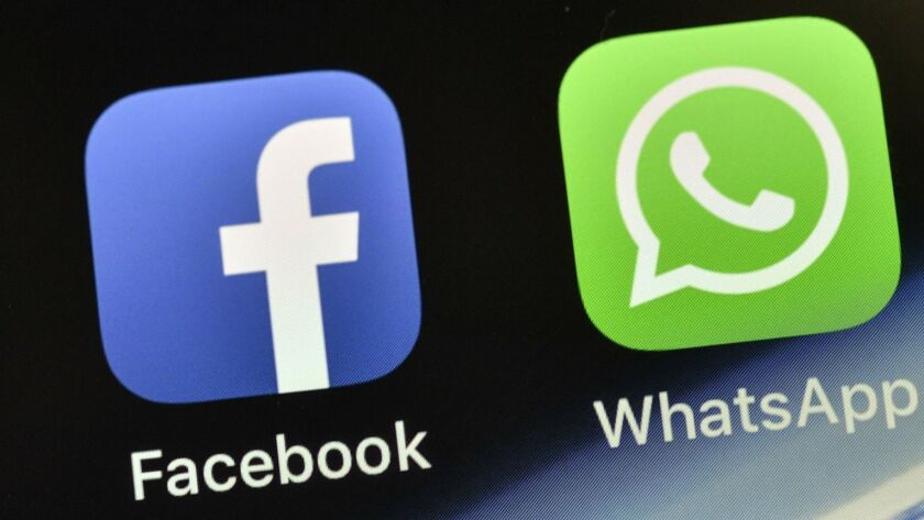 FILE - In this Nov. 15, 2018, file photo the icons of Facebook and WhatsApp are pictured on an iPhon