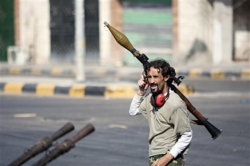 RETRANSMISSION TO ADD BYLINE - In this Wednesday, Aug. 17, 2011 photo, a Libyan rebel fighter carries a rocket-propelled grenade in Sabratha, 50 miles (75 kilometers) west of Tripoli, Libya. (AP Photo/Giulio Petrocco)