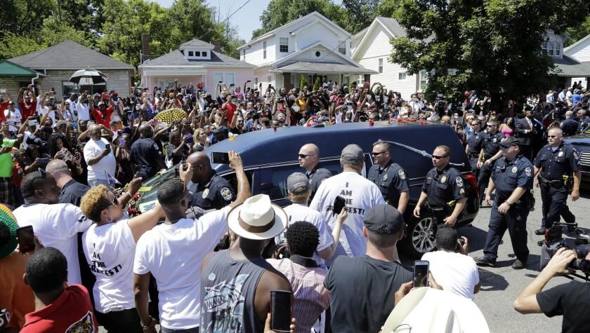 La carrosa fúnebre con el cuerpo de Muhammad Ali pasa frente a la que fue su casa en la infancia durante la procesión de despedida del campeón el viernes 10 de junio de 2016, en Louisville, Kentucy. Cientos de personas salieron a dar el último adiós al atleta más seguido y controversial del siglo 20 en su ciudad natal. (AP Foto/Mark Humphrey)