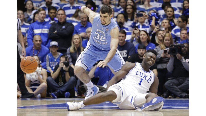 Duke's Zion Williamson falls to the floor with an injury while chasing the ball with North Carolina's Luke Maye during the first half of an NCAA college basketball game Feb. 20 in Durham, N.C.