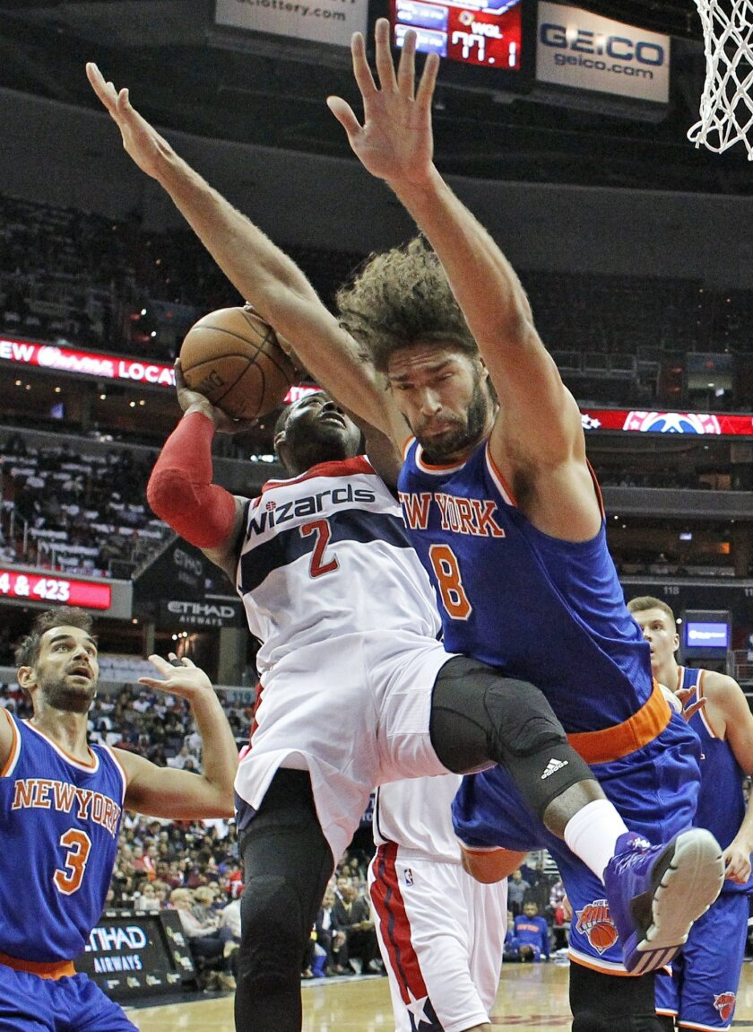 Washington Wizards guard John Wall (2) attempts to shoot as he collides with New York Knicks center Robin Lopez (8) in the first half of an NBA basketball game, Saturday, Oct. 31, 2015, in Washington. (AP Photo/Alex Brandon)