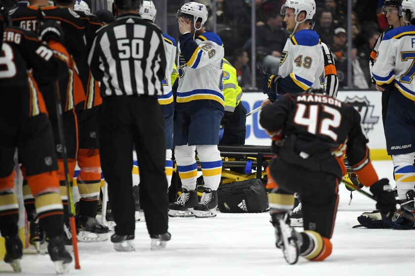 St. Louis Blues defenseman Vince Dunn, left, wipes his faces as Ducks defenseman Josh Manson kneels on the ice while medical personnel work on Blues defenseman Jay Bouwmeester.