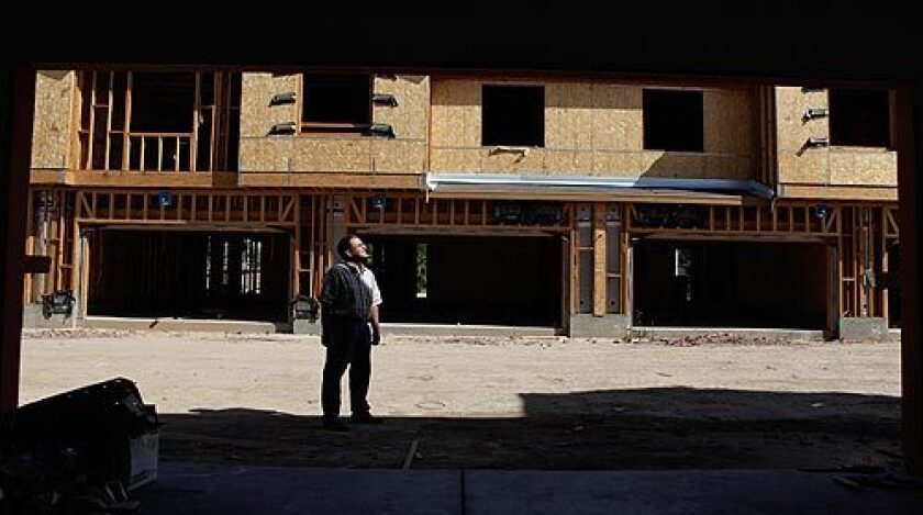 Imperial Valley real estate agent Frederic Din is framed by a vacant garage outside a partly completed home at the Springhouse development in Brawley. The builder went bankrupt and left uncompleted homes and empty lots. Audio slideshow >>>