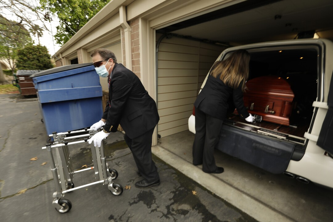 Funeral home workers followed strict protocols in handling the casket.