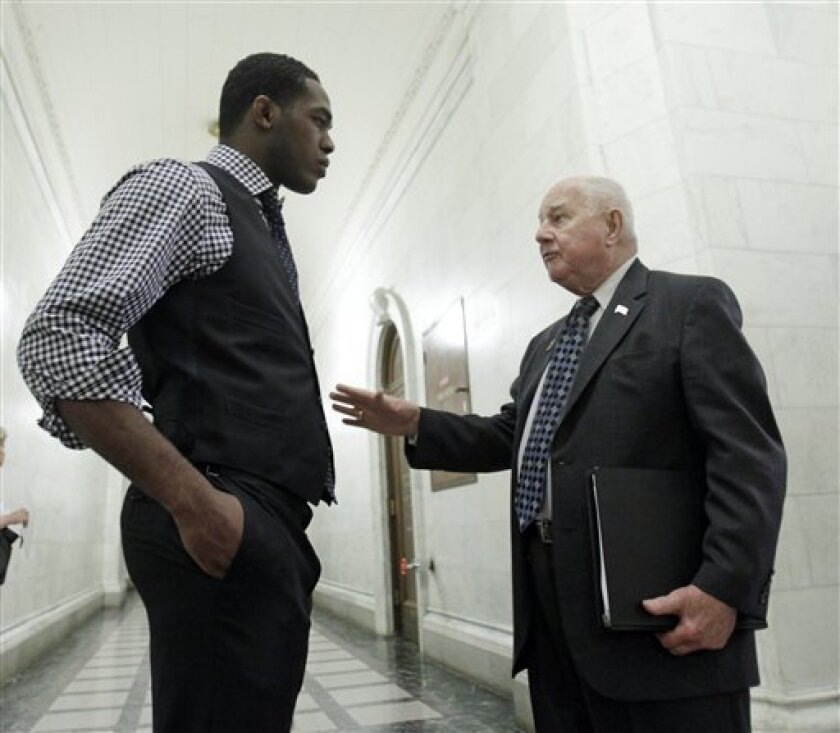 FILE - In this May 23, 2011 file photo, Ultimate Fighting Championship light heavyweight title holder Jon Jones, left, talks with Sen. William Larkin Jr., R-New Windsor, at the Capitol in Albany, N.Y. A bill to legalize MMA in New York has passed the Senate but failed again last week, still facing Assembly opposition. (AP Photo/Mike Groll, File)