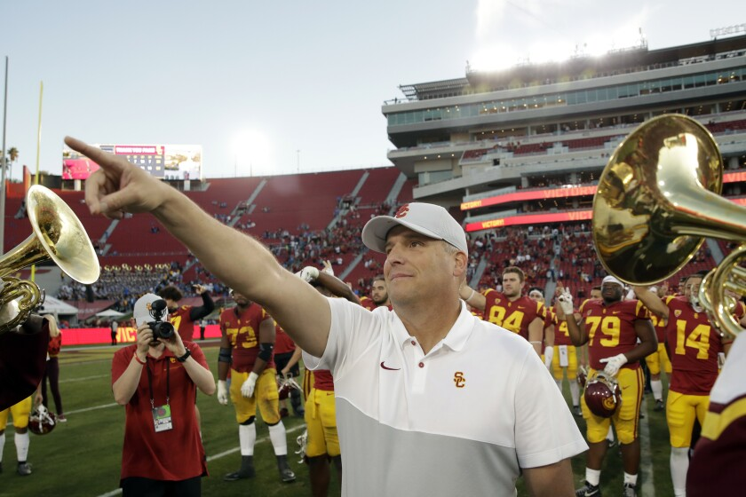 USC coach Clay Helton signals to fans after a 52-35 win over UCLA