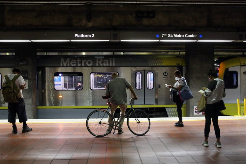 Passengers wait for the A Line on the platform of the 7th Street station.