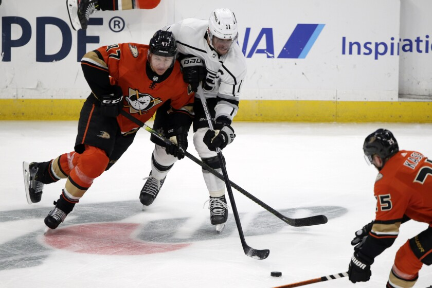 Kings center Anze Kopitar, center, competes for the puck with Ducks defenseman Hampus Lindholm.