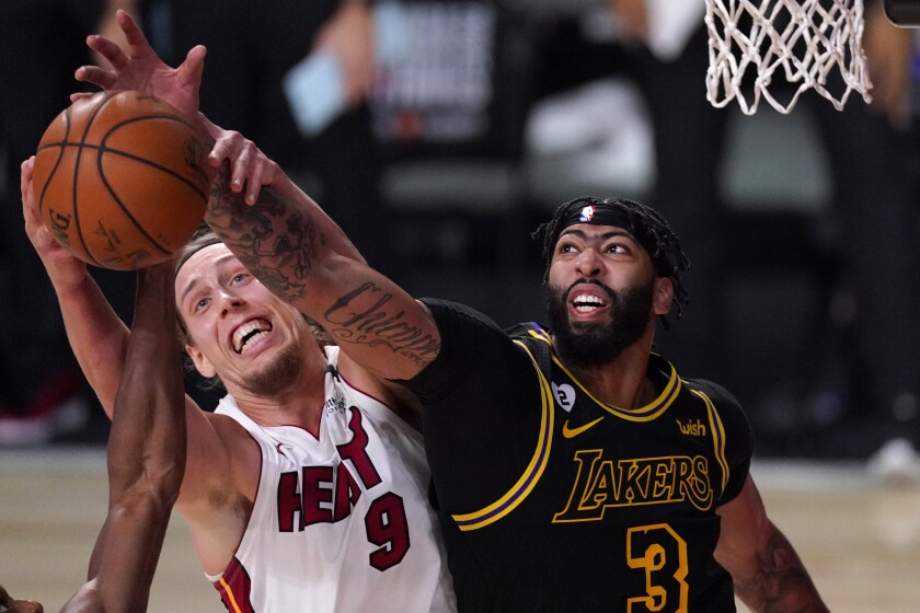 Miami Heat forward Kelly Olynyk (9) and Los Angeles Lakers forward Anthony Davis (3) compete for control of a rebound during the second half of Game 2 of basketball's NBA Finals, Friday, Oct. 2, 2020, in Lake Buena Vista, Fla. (AP Photo/Mark J. Terrill)