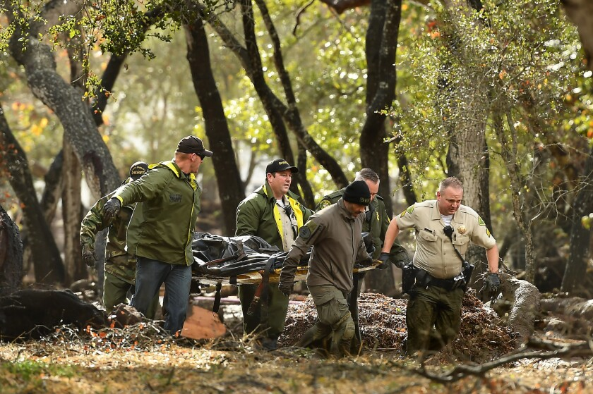 Sheriffs deputies carry a body from the debris near Hot Springs Road in Montecito after a major storm hit the burn area Tuesday.