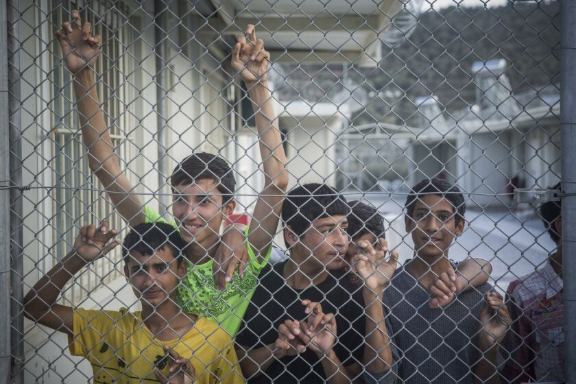 Refugees observe Greece and Austria Prime Ministers from behind a fence at the Moria camp in Lesbos island , Greece, on Tuesday, Oct. 6, 2015. The Austrian Chancellor and the Greek premier visited Lesbos island Tuesday to view first-hand the impact of the refugee crisis and tour facilities set up t