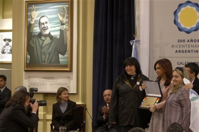 Argentina's President Cristina Fernandez, second right, poses for a photo holding a present she received from members of gays movements, after signing the same sex marriage bill at the the Latin America Patriots room of the government house in Buenos Aires, Wednesday, July 21, 2010.  (AP Photo/ Edu