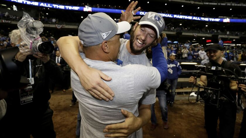 Los Angeles Dodgers' Clayton Kershaw celebrates with manager Dave Roberts after winning Game 7 of th