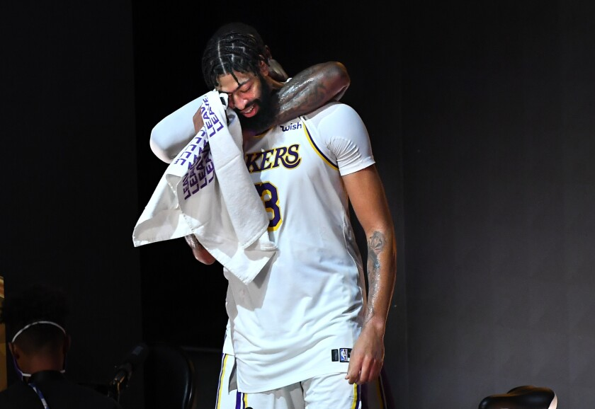 Anthony Davis is hugged from behind by LeBron James after winning the NBA title on Oct. 10, 2020, in Orlando, Fla.