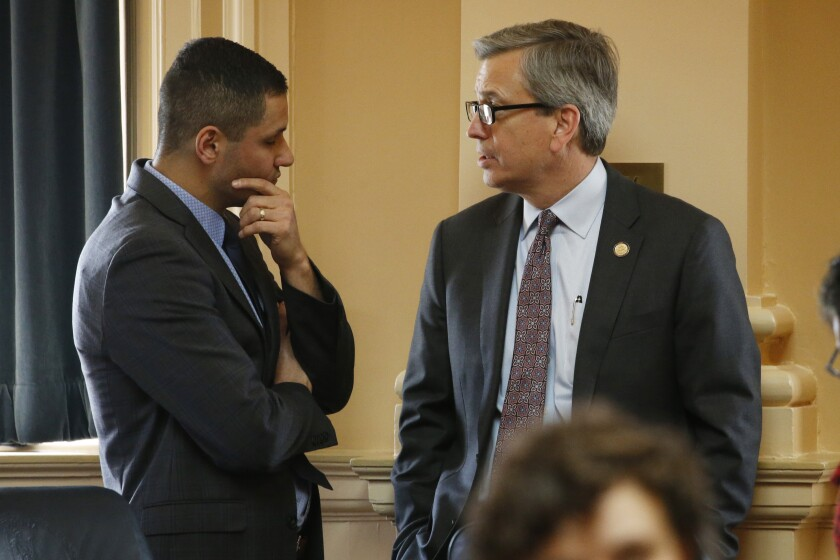 Del. Richard 'Rip' Sullivan, D-Arlington, right, talks with Del. Sam Rasoul, D-Roanoke, during the House session at the Capitol Thursday, March 5, 2020, in Richmond, Va. Sullivan is leading the floor debate on the renewable energy bills. (AP Photo/Steve Helber)