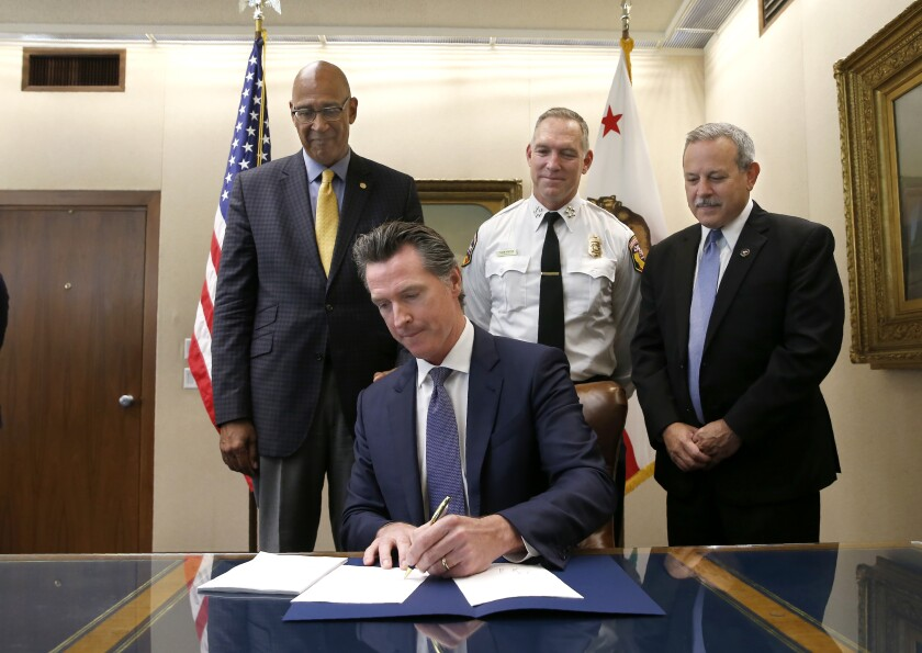 Gov. Gavin Newsom signs a measure aimed at stabilizing the state's electric utilities in the face of devastating wildfires caused by their equipment, as the bills author, Assemblyman Chris Holden, D-Pasadena, left, Thom Porter, the director for the California Department of Forestry and Fire Protection, center, and Mark Ghilarducci, the director of the California Governor's Office Emergency Services, right, look on in Sacramento, Calif., Friday, July 12, 2019.