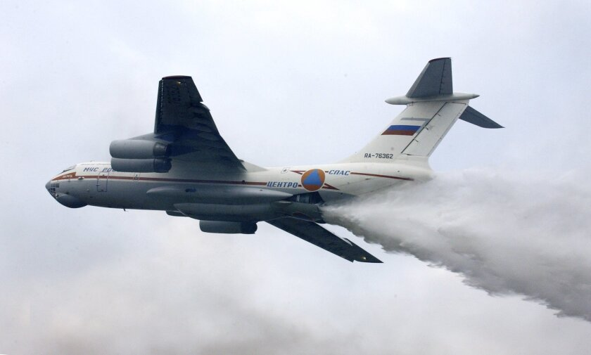 FILE - In this file photo taken on Friday, Sept. 27, 2002, an Il-76 jet releases clouds of fire-retardant chemicals during joint exercises of fire and rescue workers in Noginsk, some 68 kilometers (42 miles) east of Moscow, Russia.  Russia's Emergencies Ministry said one of its firefighting planes