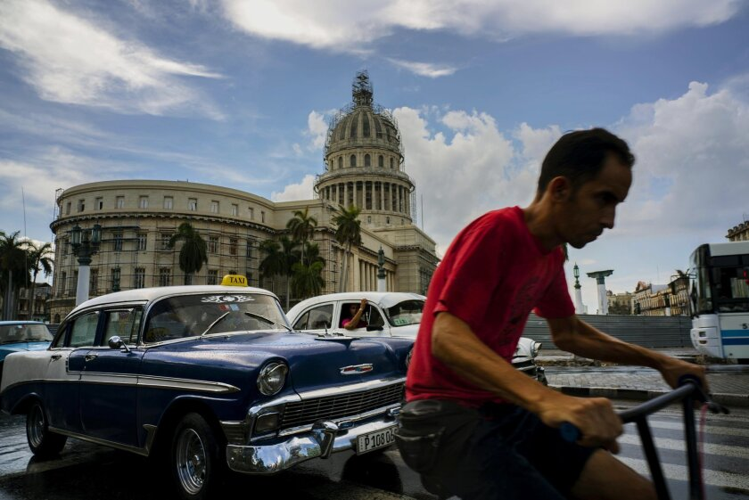 A man cycles alongside taxi drivers near the Capitol building in Havana, Cuba, Friday, July 15, 2016. Authorities warned they will pull the licenses of private taxi drivers who raise fares, after people complained that rates have doubled on some routes. Collective taxis cost about 40 cents. The warning comes as officials say the country faces months of economic and energy restrictions due in part to the crisis in Venezuela and a reduction in the amount of oil Cuba receives from its South American ally. (AP Photo/Ramon Espinosa)