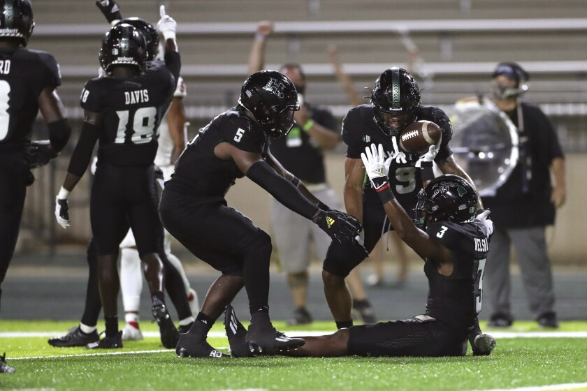Hawaii defensive back Hugh Nelson II (3) reacts with defensive back Khoury Bethley (5) and defensive back Quentin Frazier (19) after Nelson made an interception against Fresno State during the fourth quarter of an NCAA college football game, Saturday, Oct. 2, 2021, in Honolulu. (AP Photo/Marco Garcia)