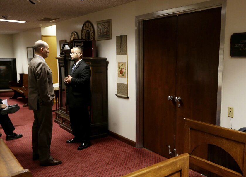 In this March 26, 2014 photo, Senate Sergant-at-Arms Gerardo Lopez, right, talks with another security officer outside a lounge where Senate Democrats were meeting at the state Capitol, in Sacramento, Calif. Lopez, the son of the Senate's human resources director, Dina Hidalgo, was fired after an investigation revealed that he was high on cocaine the night of a gunfight outside his Sacramento home where one man was killed. Secretary of the Senate Greg Schmidt has denied AP's request for a copy of a separate investigation into the management of Senate security, known as the Office of the Sergeant-at-Arms, that was driven by a criminal case involving Lopez. (AP Photo/Rich Pedroncelli, File)