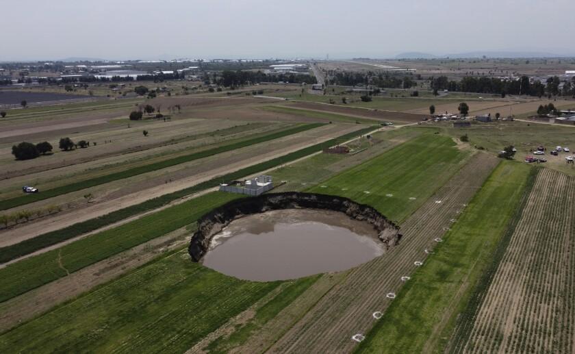 Un socavón con agua en el fondo continúa creciendo en Puebla, México.