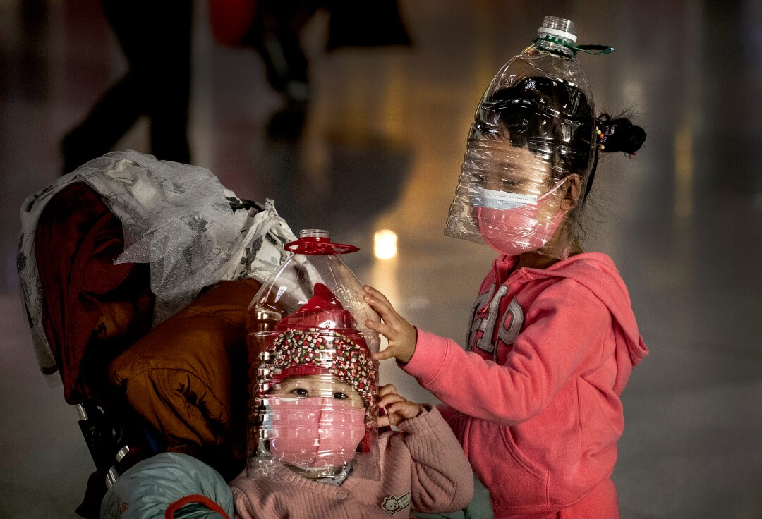 CHINA: Chinese children wear masks and plastic bottles over their faces as protection against the coronavirus while waiting to check in to a flight at Beijing Capital International Airport.