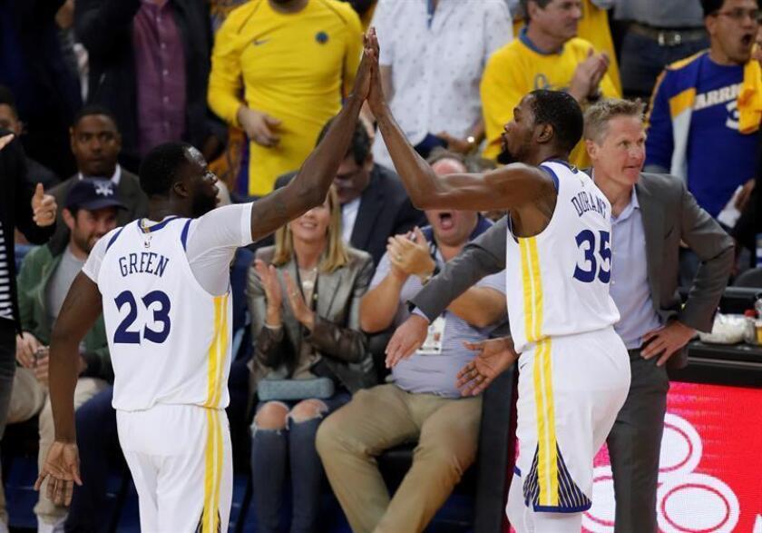 El jugador de los Warriors de Golden State Draymond Green (izq) choca los cinco con su compañero de equipo Devin Durant junto a su entrenador Steve Kerr durante el quinto partido de la serie de primera ronda de la Conferencia Oeste de la NBA de baloncesto disputado contra los Spurs de San Antonio en el estadio Oracle Arena de Oakland, California (Estados Unidos). EFE