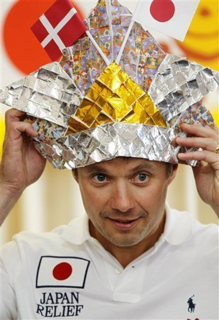 Danish Crown Prince Frederik puts on an origami, or folded paper, helmet made and presented by children during his visit to Akai Minami Nursery School in Higashimatsushima in Miyagi Prefecture Tuesday, June 14, 2011. Frederik, currently on a three-day visit to Japan, became the first foreign royal