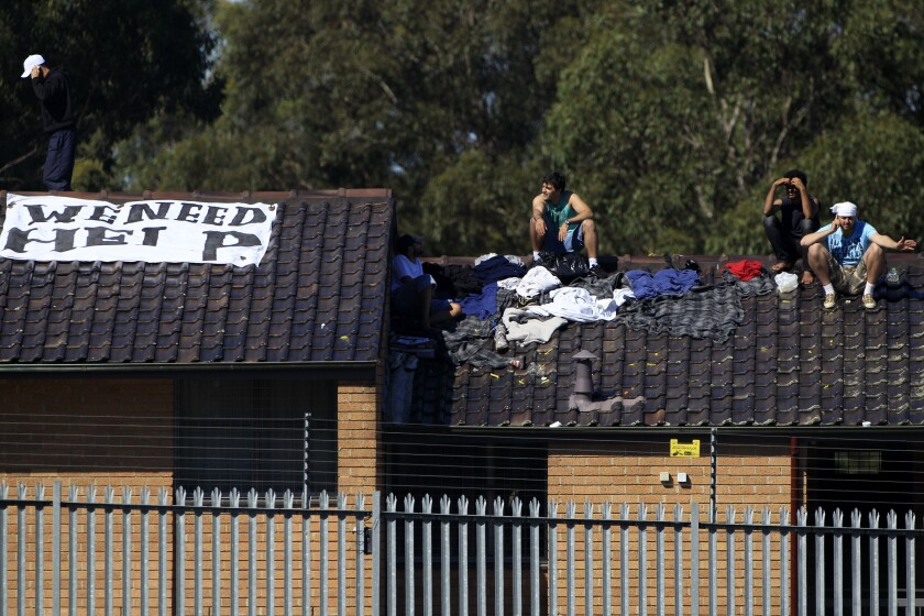 Men gather on a rooftop at the Villawood Detention Center in Sydney, Australia, in 2011.