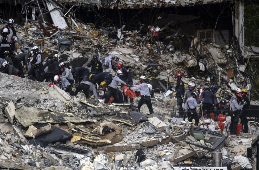 People wearing protective helmets work amid a mountain of debris.