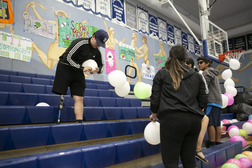 Giancarlo Gil (left), who became active in ASB, helps prepare the Chula Vista High gym for an assembly.