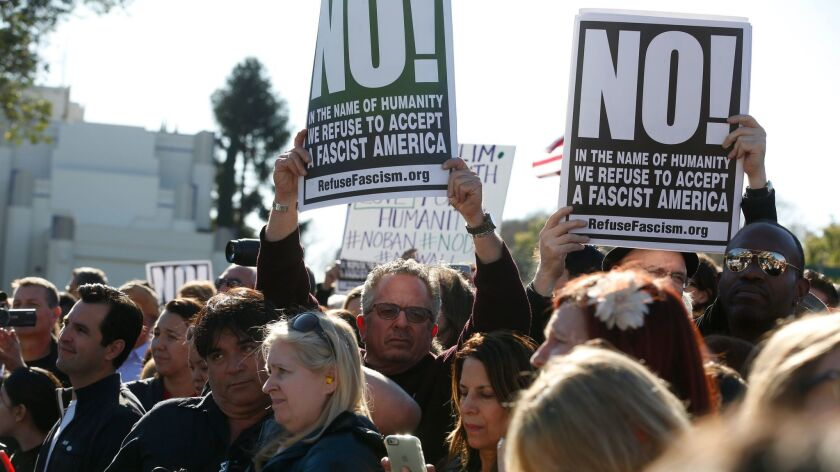 Keith James, center, of RefuseFascism.Org, holds up a sign during the United Voices rally outside United Talent Agency headquarters.