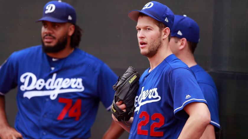 Dodgers starting pitcher Clayton Kershaw (22) stands with relief pitcher Kenley Jansen (74) and starting pitcher Rich Hill during workouts at the team's spring training baseball facility Wednesday, Feb. 14, 2018, in Glendale, Ariz.