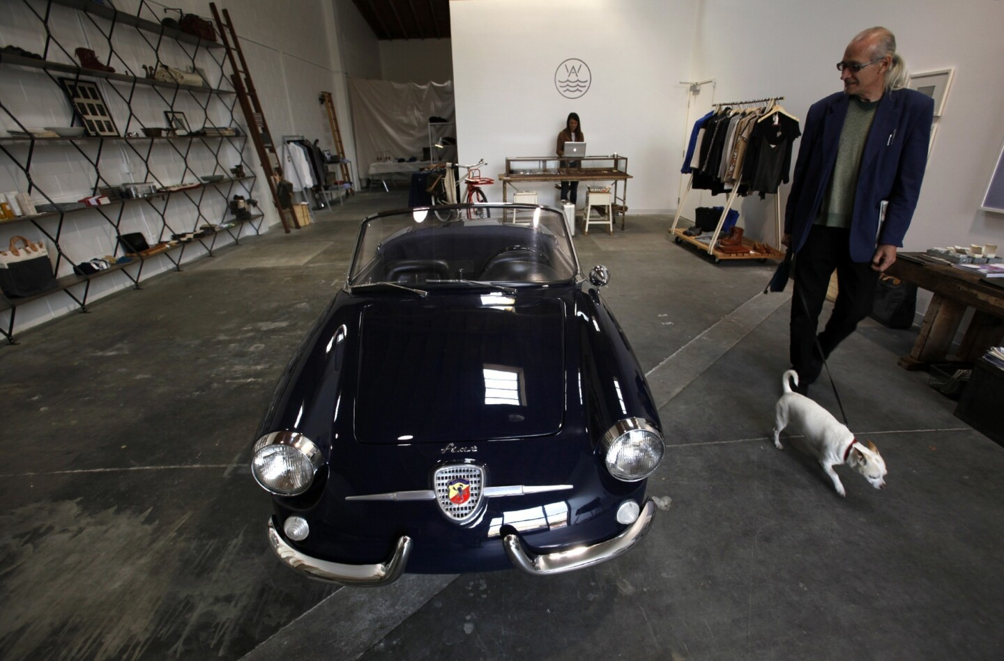 """This smartly styled design gallery opened two weeks ago with an eclectic mix including furniture by downtown designer Tim Campbell, ceramics by Echo Park potter Victoria Morris and made-in-L.A. Weiss watches. """"It's a California edit on everything,"""" creative director Raan Parton said. One exception: The 1959 Fiat Abarth 750 Spider sitting in the middle of the modern, skylighted space. Here, Drew Lesso walks past the car, which is for sale."""