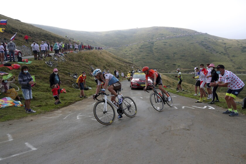 A spectator cheers France's Nans Peters, left, and Ilnur Zakarin of Russia as they climb Port de Bales pass during the stage 8 of the Tour de France cycling race over 141 kilometers (87.6 miles) from Cazeres-sur-Garonne to Loudenvielle, France, Saturday, Sept. 5, 2020. (AP Photo/Thibault Camus)