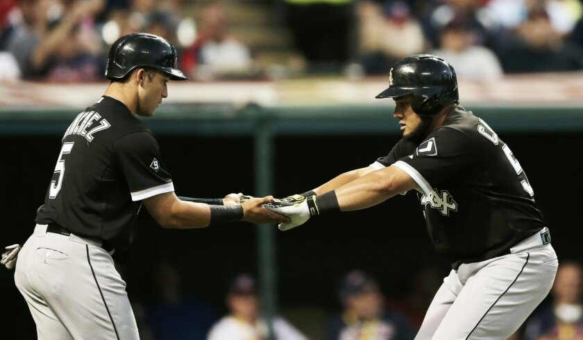 Chicago White Sox's Melky Cabrera, right, is congratulated by teammate Carlos Sanchez after hitting a two-run home run off Cleveland Indians relief pitcher Kyle Crockett in the seventh inning of a baseball game, Thursday, July 23, 2015, in Cleveland. Sanchez also scored on the play. (AP Photo/Tony Dejak)