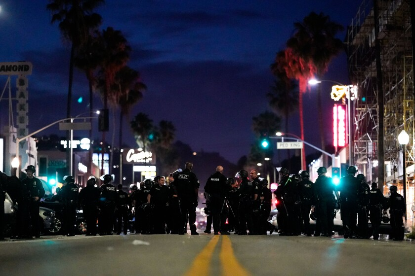 Police gather Saturday night the Fairfax District, with Canter's Deli in the background.