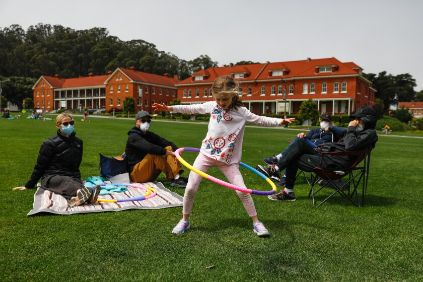 Angie Muscat, 6, hula hoops as mom Christina Dam (left), dad Jason Muscat (second from left), grandmother Becky Muscat (second from right) and grandfather Bob Muscat (right) look on at the Main Parade Grounds in the Presidio in San Francisco.