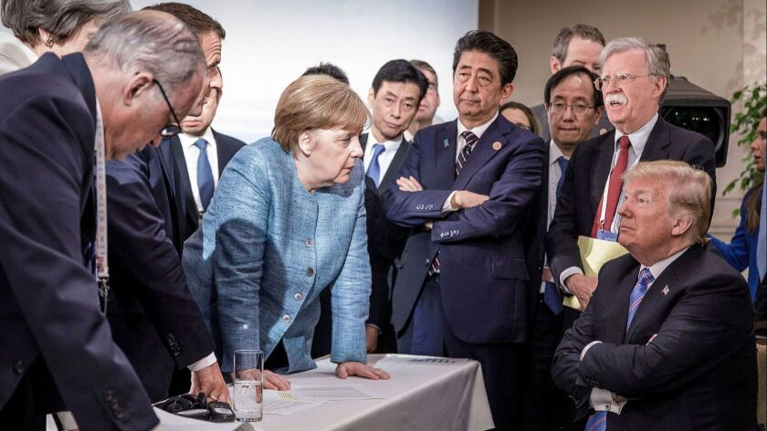 In a German government photo, German Chancellor Angela Merkel leans in while speaking to President Trump during a gathering of G-7 leaders and aides Saturday in Canada.