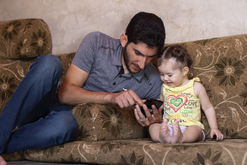 Abdel Hamid Yousef plays with his 11-month-old daughter, Aya, at a settlement for the displaced near the town of Atmeh in northern Syria on Sept. 1, 2019. He lost his twin infants, his wife and 16 other relatives in the poison gas attack that hit Syria's Khan Sheikhoun in April 2017.