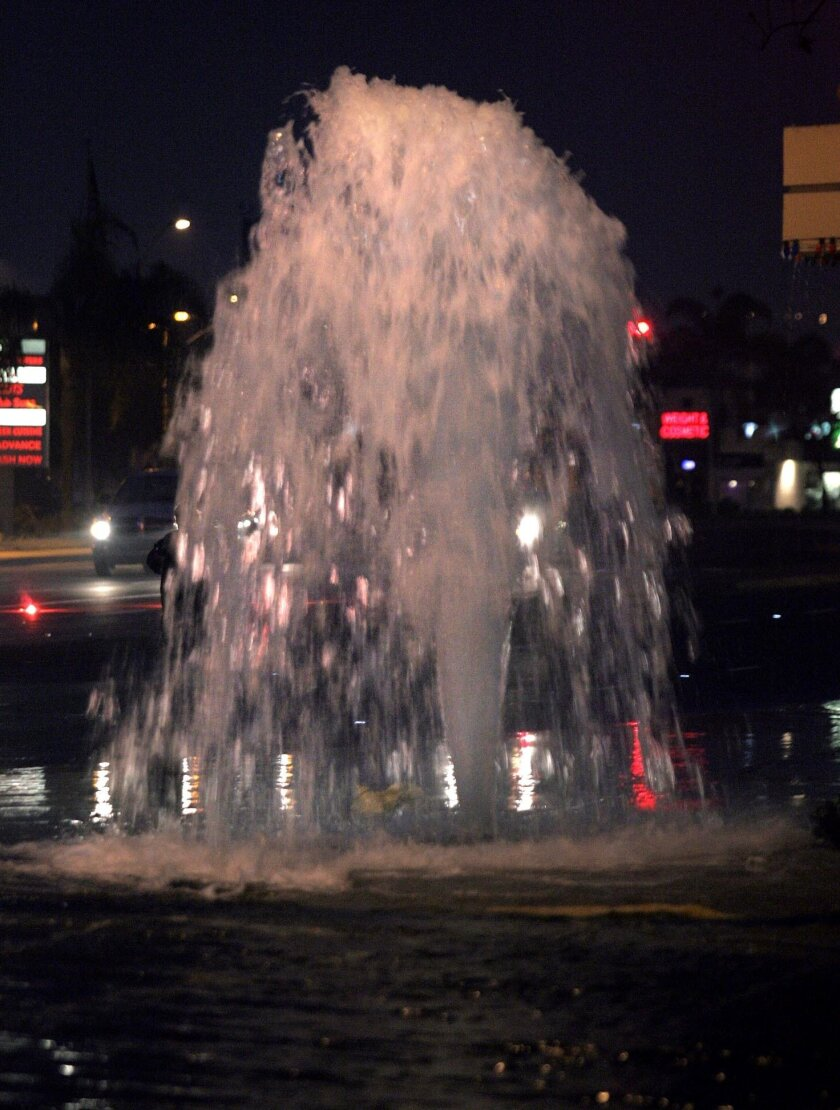Water gushes from a broken  fire hydrant at the corner of Rosecrans Street and Midway Drive.