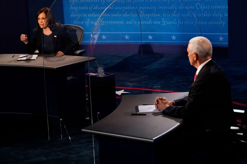 Vice President Mike Pence listens to Kamala Harris during their debate