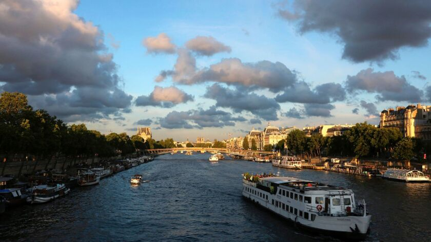 Tourist river boats sail on the Seine in Paris. It's been a banner year for vacation spending, here and abroad.
