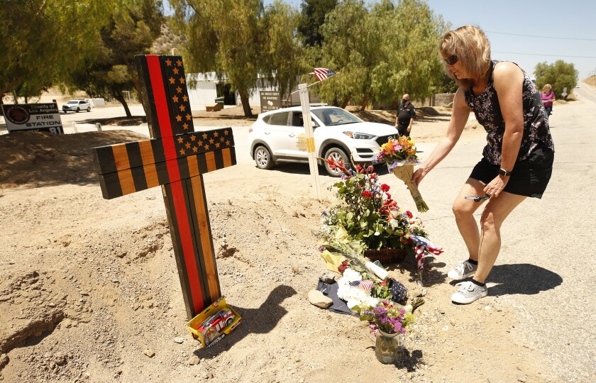 A woman places flowers in front of a wooden cross in the dirt