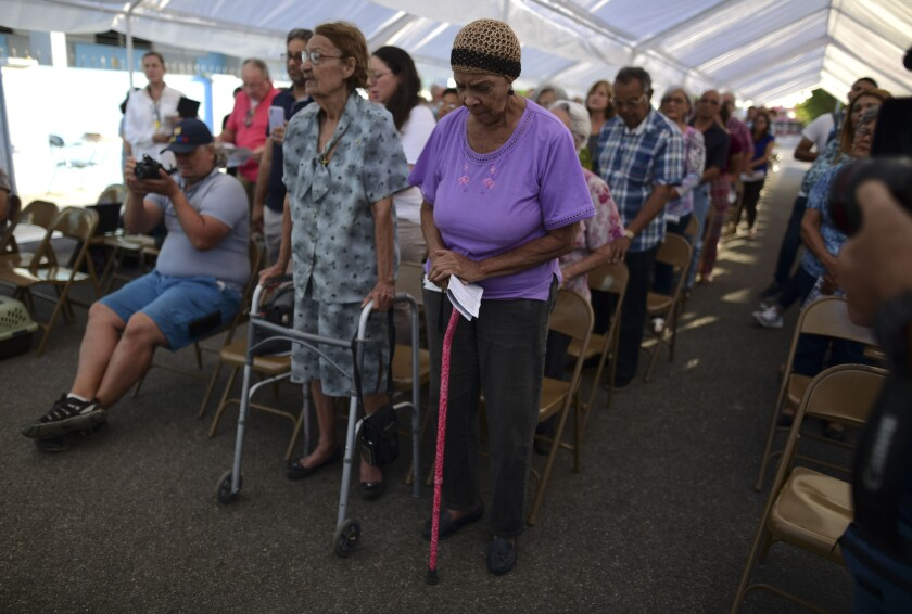 People attend an outdoor Mass on Saturday under a tent set up near the Immaculate Conception Catholic Church in Guanica, Puerto Rico, after a magnitude 5.9 quake earlier in the day.