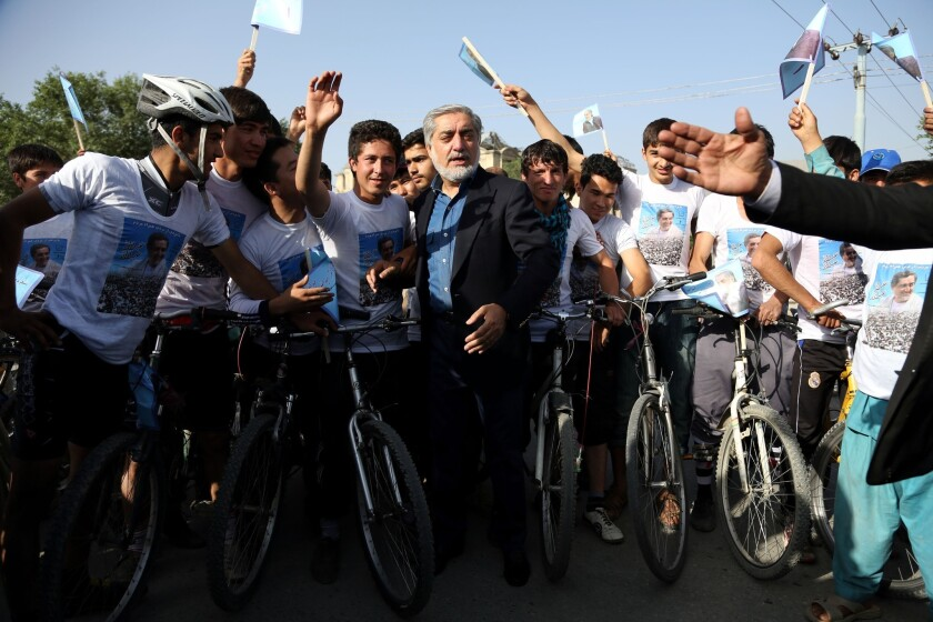 Afghan presidential candidate Abdullah Abdullah talks with supporters at a cycling event in Kabul shortly before two blasts struck his convoy.