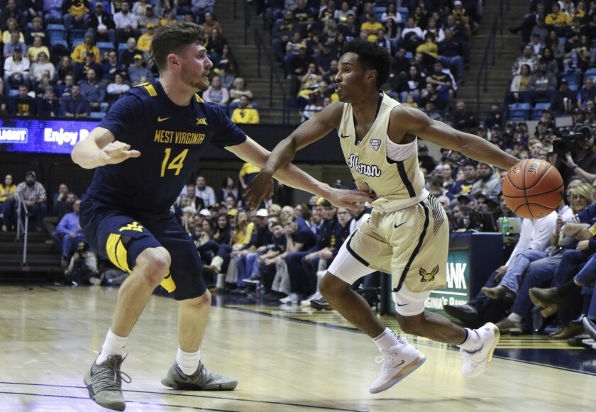 Akron's Loren Cristian Jackson is defended by West Virginia's Chase Harler during an NCAA college basketball game, Friday, Nov. 8, 2019, in Morgantown, W.Va. (AP Photo/Kathleen Batten)