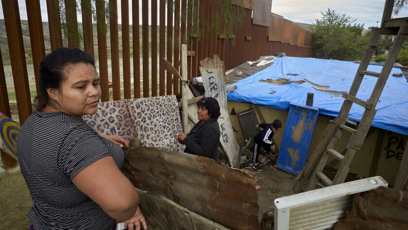 Yuli Arias, left, stands near a newly-replaced section of the border wall as her mother, Esther Arias, center, stands in the family's house that was once threatened by construction along the border in Tijuana, Mexico.