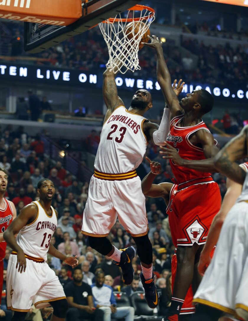 Cleveland Cavaliers forward LeBron James (23) gets past Chicago Bulls forward Bobby Portis (5) for a basket during the first half of an NBA basketball game in Chicago, on Friday, April 9, 2016.  (AP Photo/Jeff Haynes)